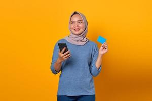 Cheerful Asian woman holding mobile phone and showing credit card photo