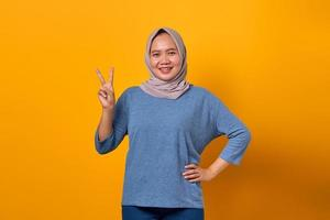 Portrait of cheerful Asian woman standing and doing victory sign photo