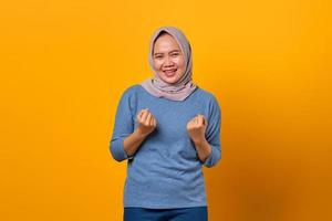 Portrait of cheerful attractive Asian woman celebrating success photo