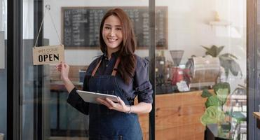 Portrait of a smiling Asian entrepreneur standing behind her cafe photo