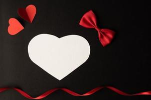 A white heart, a bow, a ribbon, and a red heart are placed photo