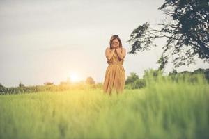 Tristeza mujer de pie con la mano cubriendo su rostro en el campo de hierba foto
