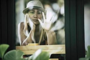 Beautiful girl sitting sad at the window in cafe photo