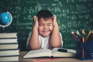 worried boy In classroom with hands on head photo