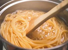 Raw spaghetti is being cooked in boiling photo