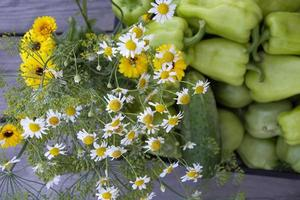 A bouquet of wildflowers and vegetables in a black box close-up photo