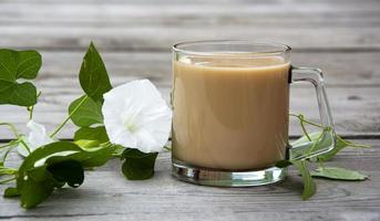 Mug with cocoa and loach with white flowers on a wooden background photo