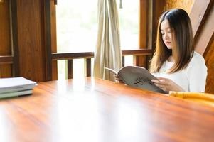beautiful woman sitting in a cafe reading a book photo