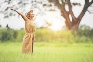 mujer joven de pie en el campo de hierba levantando las manos en el aire. foto