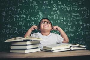 niño pensativo con libro en el aula foto