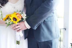A couple holding a bouquet of flowers on the wedding day photo