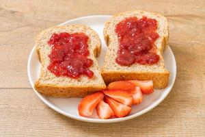 whole wheat bread with strawberry jam and fresh strawberry photo