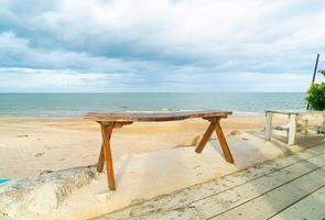 wood bench on beach with sea beach background photo