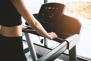 Asian sport woman walking or running on treadmill photo