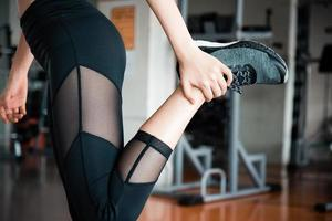 Estirar las piernas con las manos antes de entrenar y hacer ejercicio. foto