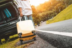 Back view of yellow suitcase dragging baggage suitcase alone road photo