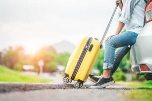 Closeup lower body of woman relaxing on car trunk with trolly luggage photo
