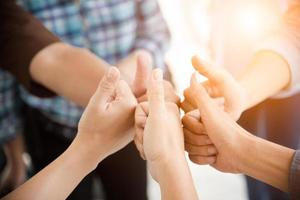 People thumb up in teamwork group photo
