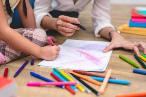 Closed up hands of mom teaching little children drawing photo