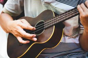 Primer plano de la mano del guitarrista tocando la guitarra. concepto de instrumento musical foto