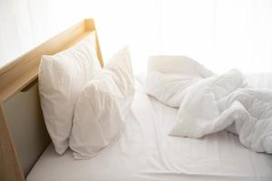 White unmade bed in the morning with sunshine photo