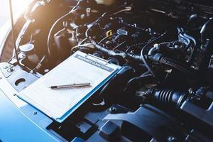 Clipboard on car with car insurance claim form customer maintenance photo