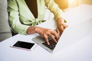 Closeup of woman hand working at home office and typing on keyboard photo