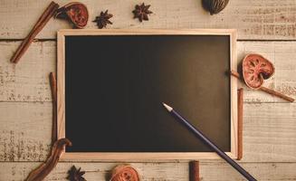 Pizarra de madera vacía sobre un piso de madera con lápiz y hojas secas foto