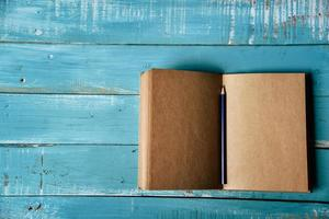 Top view of blank open notebook on blue wooden background photo