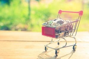 Carro de compras en la mesa de madera con monedas en el fondo de la naturaleza al aire libre foto