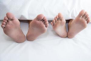 Close up of couple barefoot under blanket in bedroom in honeymoon photo