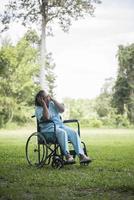 Lonely elderly woman sitting sad feeling on wheelchair at garden photo