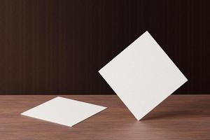 White square shape paper business card mockup on wooden brown table photo