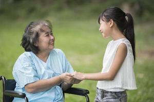 abuela anciana en silla de ruedas con nieta foto
