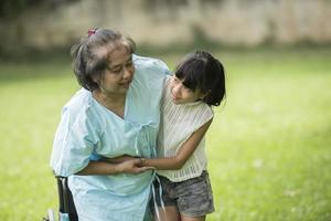 abuela anciana en silla de ruedas con su nieta en el hospital foto