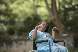 Anciana sentada en silla de ruedas con enfermedad de Alzheimer foto