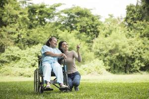 nieta hablando con su abuela sentada en silla de ruedas foto