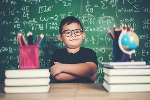 niño pensativo con libro cerca de una junta escolar foto