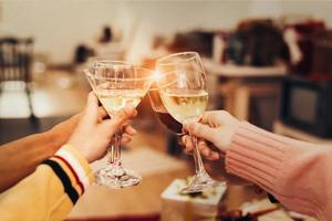 Manos de personas celebrando la fiesta de año nuevo en casa con vaso para beber foto