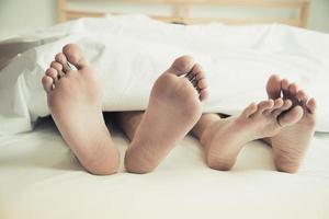 descalzo de los amantes debajo de la manta en el dormitorio. vacaciones y felicidad foto