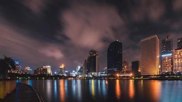 Big city in the night life with reflection of water wave photo