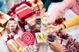 Manos de personas celebrando la fiesta de año nuevo en casa con vino bebiendo foto