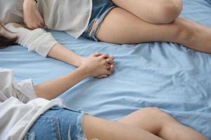lesbianas durmiendo y tomados de la mano en la cama juntos foto