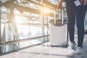 Close up of woman traveling and holding trolley suitcase in airport photo