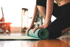 Close up of sporty woman folding yoga mattress in sport fitness gym photo