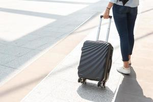 Close up woman and suitcase trolley luggage in airport photo