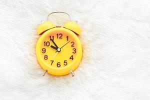 Despertador amarillo sobre lana blanca. concepto de tiempo tardío y perezoso foto