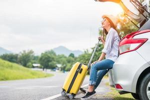 Asian woman spending weekend in roadtrip with yellow luggage photo