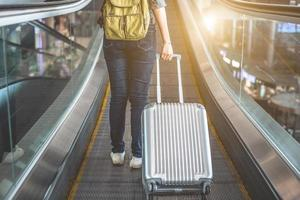 Back view of beauty woman traveling and holding suitcase on escalator photo