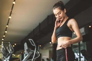 Deporte feliz mujer delgada con línea de cinta de cintura en el gimnasio foto